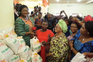Wife of Ondo State Governor, Olukemi Mimiko, (left) presenting food palliative to one of the beneficiaries of the Ondo State Food Palliatives Programme, Adedoyin Febisola (middle), at the official inauguration of the programme, in Ikare-Akoko, on Tuesday.