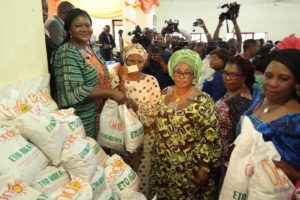 Wife of Ondo State Governor, Olukemi Mimiko, (left) presenting food palliative to one of the beneficiaries of the Ondo State Food Palliatives Programme, Orungbemi Toyin (2nd left), while Commissioner for Women Affairs, Olasimi Akindele-Odunbaku (middle) and others watch, at the official inauguration of the programme, in Ikare-Akoko, on Tuesday.