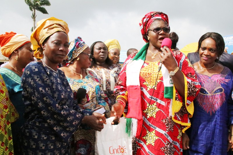 Wife of Ondo State Governor, Olukemi Mimiko (2nd right), presenting a bag of rice to one of the beneficiaries of the Food palliative programme, Fayemiro Omolade (left),