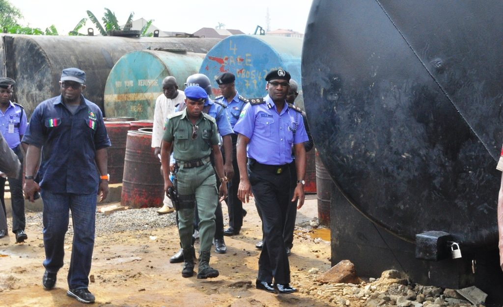 Lagos State Police Commissioner, Mr. Fatai Owoseni (right), with the Permanent Secretary, Lands Bureau, Lagos State Governor's Office, Mr. Bode Agoro (left) at the site of an illegal Oil Depot during the arrest of its Operators in Oregun, Onigbongbo LCDA