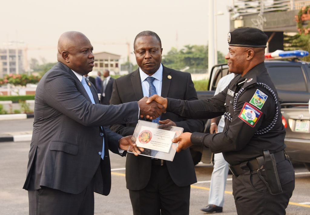 Lagos State Governor, Mr. Akinwunmi Ambode (left), being presented with the Best Security and Safety Conscious award given to the State Government in South Africa by Commander, RRS, ACP Tunji Disu (right) while Permanent Secretary, Office of Chief of Staff, Mr. Abiodun Bamgboye (middle), watches during the handing over of 3 Patrol Vehicles and 45 Power Bikes to the Rapid Response Squad (RRS) at the Lagos House, Ikeja